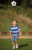 Latino boy playing with soccer ball Royalty Free Stock Photography
