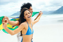 Latino brasil couple. Latino hispanic couple are Brasil fans and hold flag having fun together Stock Images