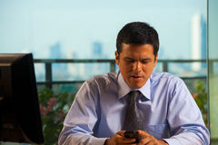 Latino Businessman Receives Bad News. A hispanic businessman receives bad news by text (sms) on his smartphone.  30s latino American male of mixed Brazilian Stock Image