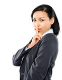 Latino businesswoman finger on lips white background Royalty Free Stock Image