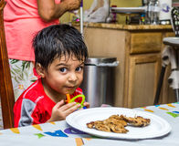 Latino Child Sitting at a Table with Food. On a plate in front of him, holding a sippy cup and looking at the camera with a mischievous look on his face Royalty Free Stock Image