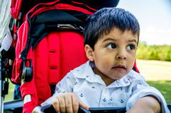 Latino child in a stroller. Close up shot of latino child sitting in a red stroller outside and looking off to the side Stock Photo