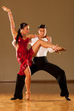 Latino dance couple in action - dancing wild samba. In ballroom Royalty Free Stock Images