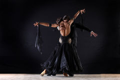 Latino dancers in ballroom. Against on black background Stock Photo