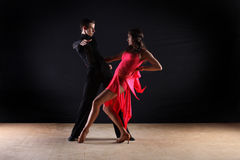 Latino dancers in ballroom. Against on black background Stock Images
