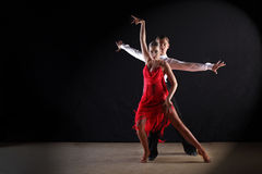 Latino dancers in ballroom. Against black background Stock Images