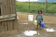 Latino girl goes to fetch water in mountain landscape royalty free stock image