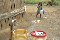 Latino girl goes to fetch water in mountain landscape. Nicaragua, department Nueva Segovia, Ocotal city: in a suburb of the town is a toddler, get to fetch stock photography