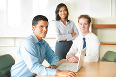 Latino Male Meeting Leader Diverse Team. A latino businessman leads a diverse team of business people including an attractive Asian woman and caucasian male Royalty Free Stock Photo