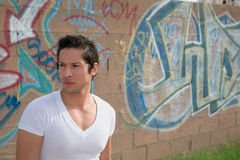 Latino Male In Urban Setting. Young latino male standing in front of graffiti Stock Photo