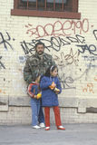 Latino man and daughters standing in front of graffiti covered walls, South Bronx, New York Stock Image