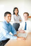 Latino Man Leading Business Meeting. A latino men leads a business meeting with two colleagues Stock Photo