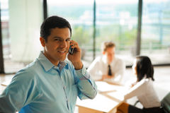 Latino Man Phone Call Business Meeting. A latino male answers a phone call during a business meeting with his colleagues Royalty Free Stock Image