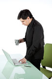 Latino man standing and working at a laptop Stock Image