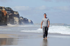 Latino man walking on a beach Royalty Free Stock Images