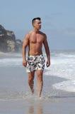 Latino man walking on a beach Royalty Free Stock Photography