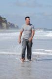 Latino man walking on a beach Stock Image