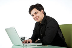 Latino man working at a laptop computer Stock Images