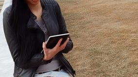 Latino meisje die met tabletcomputer in openlucht werken stock video