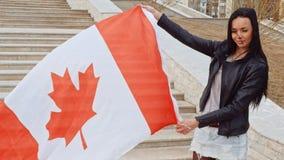 Latino meisjesactivist die met golvende de natievlag van Canada in handen camera en het glimlachen FHD lengte bekijken stock footage