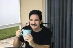 Latino mens zit en nipt van zijn kop Stock Afbeelding