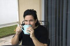 Latino mens zit en nipt van zijn kop Stock Fotografie