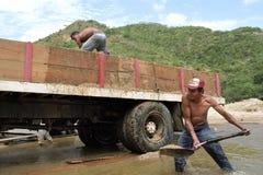 Latino Mensen die vrachtwagen met zand met schop laden Stock Afbeelding