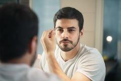 Latino mensen in orde makende wenkbrauw voor lichaamsverzorging in badkamers Royalty-vrije Stock Foto's