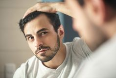 Man worried for alopecia checking hair for loss. Latino person with beard grooming in bathroom at home. White metrosexual man worried for hair loss and looking royalty free stock images