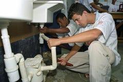 Latino tienerjaren leren beroep van loodgieterswerk, handelsschool royalty-vrije stock afbeelding