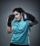 Latino woman boxer. Hispanic woman boxer delivering a hook punch Royalty Free Stock Photography
