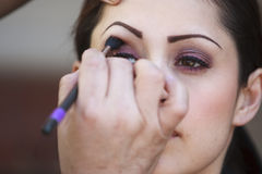 Latino Woman Having Make-up Applied To Her Eyes Stock Photo
