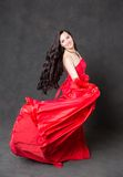 Latino Woman with long hair  in red waving dress dancing  in action with flying fabric Royalty Free Stock Photos