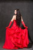 Latino Woman with long hair  in red waving dress dancing  in action Royalty Free Stock Images