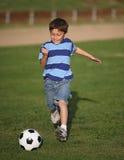 Latinojunge, der mit Fußballkugel spielt Lizenzfreies Stockbild