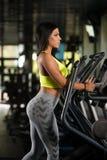 Latinokvinnor på den ellipsformiga trampkvarnen i konditionidrottshall Royaltyfria Foton