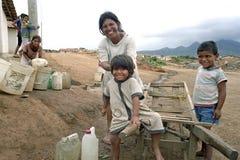 Latinomutter, Kinder holen Wasser, Schubkarre Stockbilder