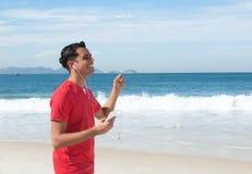 Latinsk grabb på stranden som lyssnar till musik på telefonen arkivbild
