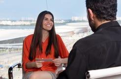 Latinsk kvinnlig presentatör som frågar en berömd kändis på tvstudion royaltyfri fotografi