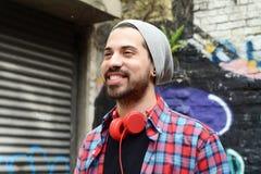 Latinsk man med röd hörlurar utomhus Fotografering för Bildbyråer