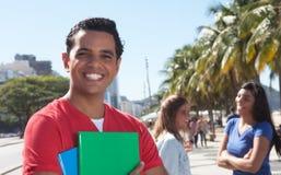 Latinsk manlig student med vänner i staden arkivfoto
