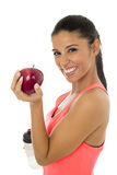 Latinsk sportkvinna i konditionkläder som äter att le för äpplefrukt som är lyckligt i sund näring Royaltyfri Foto