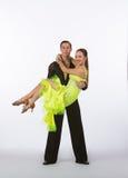 Latinska balsaldansare med den lyftneongulingklänningen - Royaltyfria Foton