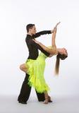 Latinska balsaldansare med neongulingklänningen - tillbaka krökning Arkivfoto