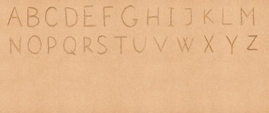 Latinskt alfabet för handskrift på sanden med royaltyfria bilder