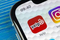 Latir o ícone da aplicação no close-up da tela do iPhone X de Apple Ícone do app do ganido yelp aplicação de COM Rede social Medi Imagem de Stock
