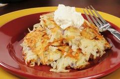 Latkes de la patata rematados con crema agria Fotografía de archivo