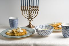 Latkes on a plate, Hanukkah, cups with milk on a white tablecloth. Horizontal