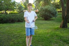 Lato śmieszny portret śliczny chłopiec dzieciak bawić się badminton w zieleń parku Zdrowy Styl życia zdjęcia royalty free