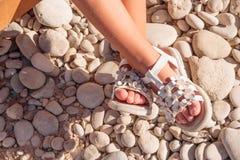 Lato bielu buty dla dzieciaków, dziecka ` s kapcie, plażowi moda dla dziecka, Kolorowa sandałów buty i kamienie, wakacje Fotografia Royalty Free